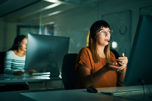 Cropped shot of an attractive young female call center agent working late at night in her office