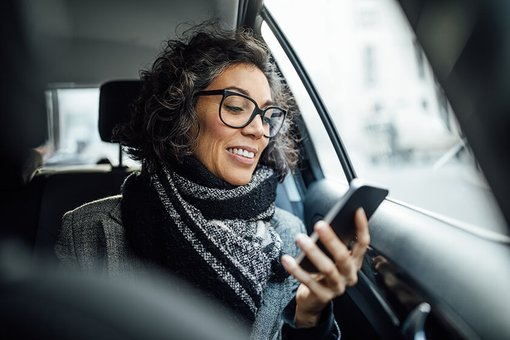 passenger woman in car looking at phone
