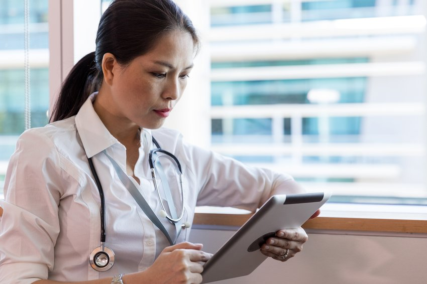 Doctor checking tablet for patient information