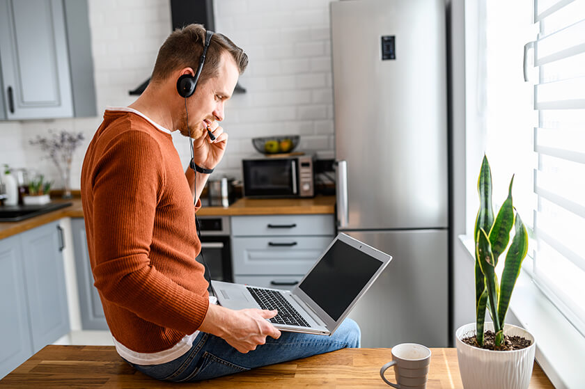 man holding laptop in kitchen with headset remote working