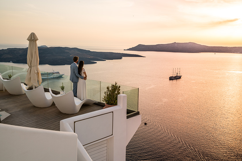 couple in lromantic location - luxury hotel in greece overlooking the sea.